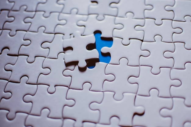 Puzzle mit einem fehlenden fehlenden aufschlussreichen blauen hintergrund