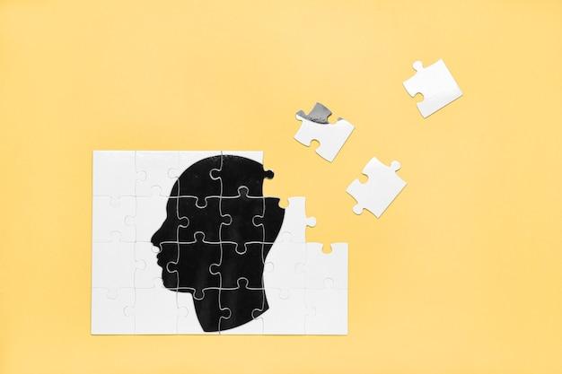 Puzzle mit gezeichnetem menschlichem kopf auf farboberfläche. konzept der demenz