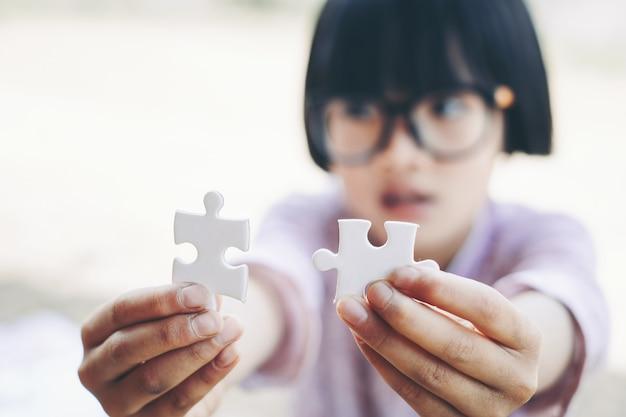 Puzzle-spiel: hände eines kleinen mädchens, das zwei stücke eines puzzlespiels hält und zusammenbringt.