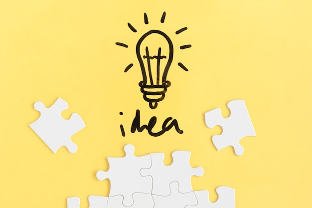 Puzzle und glühlampe mit ideenwort auf gelbem hintergrund