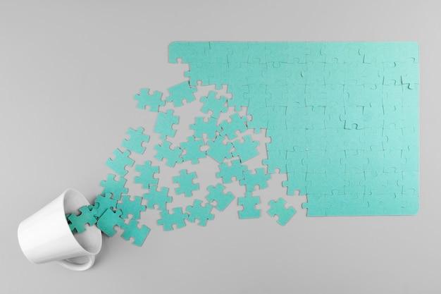 Puzzle und tasse auf grauem hintergrund