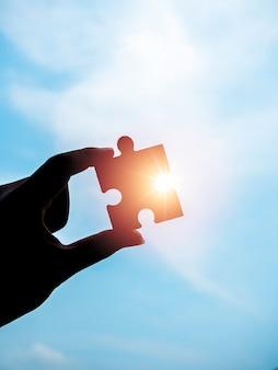 Puzzle vor blauem himmelshintergrund, silhouette, vertikaler stil. hand des geschäftsmannes, der ein puzzlespiel mit sonnenlicht und sonnenstrahlen hält. geschäftslösungen, erfolg, partnerschaft und strategiekonzept.