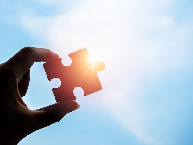 Puzzle vor hintergrund des blauen himmels mit kopienraum, silhouette. hand des geschäftsmannes, der ein puzzlespiel mit sonnenlicht und sonnenstrahlen hält. geschäftslösungen, erfolg, partnerschaft und strategiekonzept.