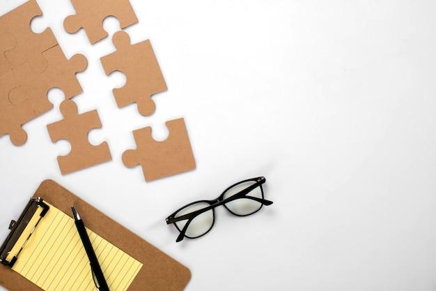 Puzzlegläser und gelber notizblock