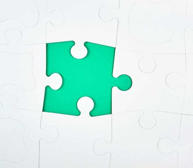 Puzzlespiel aus weißen papierstücken, die auf grün miteinander verbunden sind