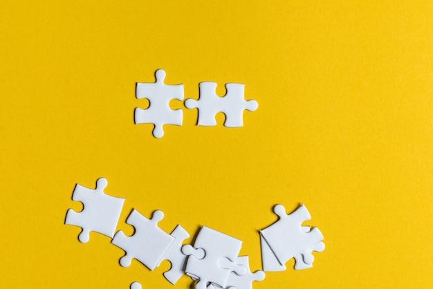 Puzzlespiele platziert auf ein kreatives konzept des gelben hintergrundes mit kopienraum