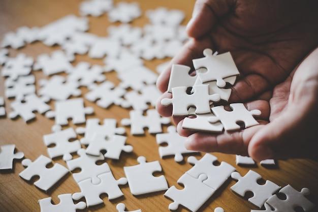Puzzlespielstücke auf palme, puzzlespielstücke in den händen des mannes