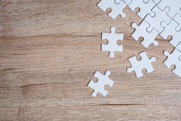 Puzzleteile auf hölzerner tabelle. business-lösungen, missionsziel