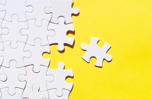 Puzzleteile auf leuchtendem gelbem hintergrund