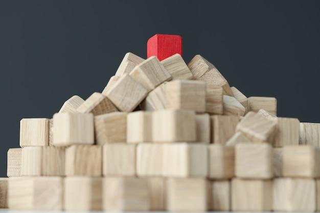 Pyramide aus beigefarbenen würfeln oben mit einem einzelnen roten auf dem tisch, individueller ansatz für jeden kunden