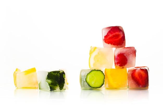 Pyramide der eiswürfel mit früchten auf einer hellen weißen oberfläche. das konzept von heißem sommer, dessert, eis. flache lage, draufsicht