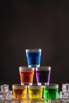 Pyramide der schüsse mit buntem alkohol auf eis