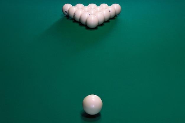Pyramide der weißen kugeln mit zahlen für russisches billard auf einem grünen tisch, nahaufnahme. ball of cue ball, zerschmettert und zielt auf ein dreieck von 15 weißen bällen