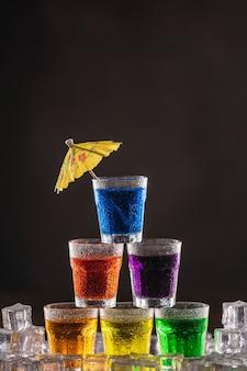 Pyramide von aufnahmen mit buntem alkohol, dekoriert mit regenschirmen für cocktails