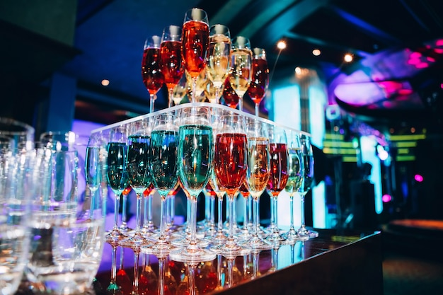 Pyramide von champagnergläsern. viele gläser champagner an der bar. champagnerblasen in einem glas. farbiger champagner.