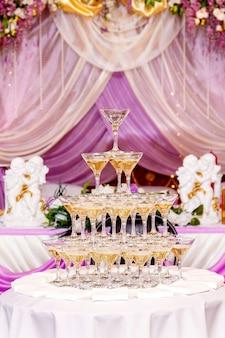 Pyramide von gläsern mit champagner im purpurroten hochzeitsinnenraum.