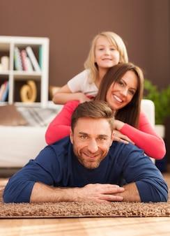 Pyramide von liebevoller familie auf teppich