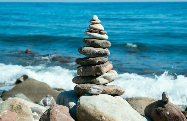 Pyramide von steinen am strand mit hellem sonnenschein. krim. russland.