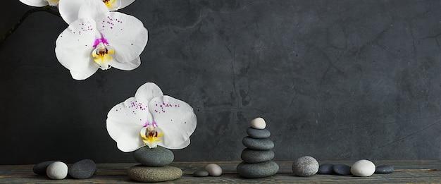 Pyramide von steinen und orchideenblumen auf einem hellgrauen hintergrund