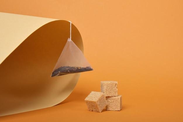 Pyramidenförmiger teebeutel und rohrzuckerwürfel auf braun gerolltem papierhintergrund, kopierraumfarbtrend
