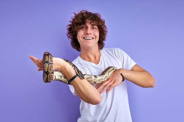 Pythonschlange, die sich um die hand des mannes wickelt, fröhlicher kerl genießt, mag exotische tiere