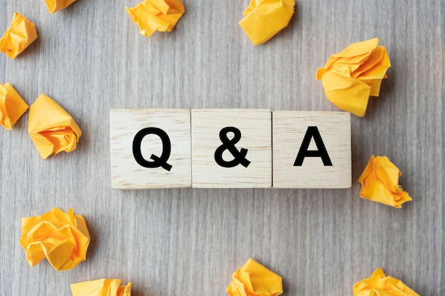 Q & a-wort mit hölzernem würfelblock und gelb zerbröckelte papier
