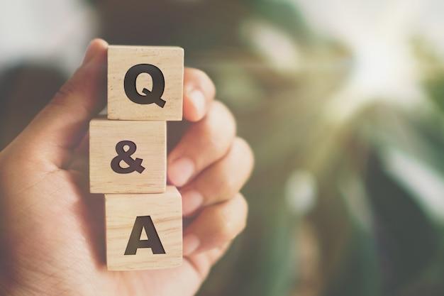 Q und a alphabet auf holzwürfel in der hand. frage und antwort bedeutungskonzept.