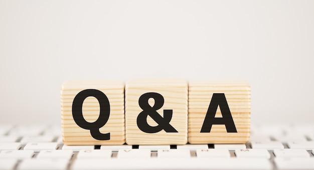 Qa oder fragen und antworten auf schwarzem block mit tastatur