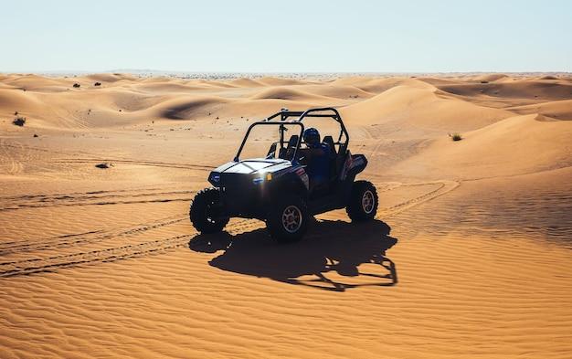 Quad-buggy-auto in sanddünen mit sonneneruption am scheinwerfer, viel spaß bei extremer dubai-safari-tour