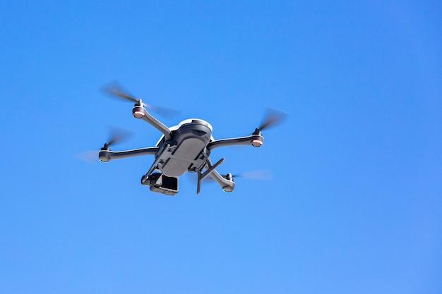 Quadcopter brummen mit der kamera gegen den blauen himmel
