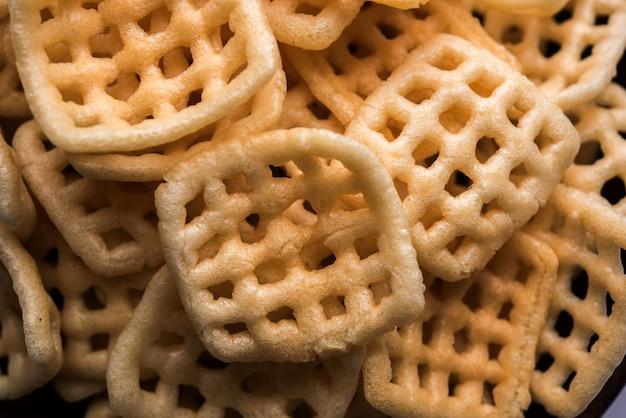 Quadratisch kariertes fryums papad ist ein knuspriges snack-pellets, das in einer schüssel serviert wird