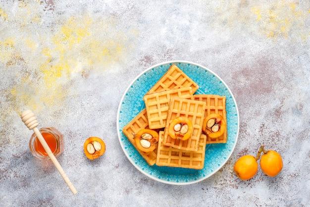 Quadratische belgische waffeln mit wollmispelfrüchten und honig