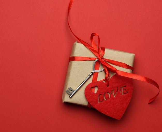 Quadratische box mit roter seidenschleife und textilherz auf rotem hintergrund, draufsicht, valentinstag