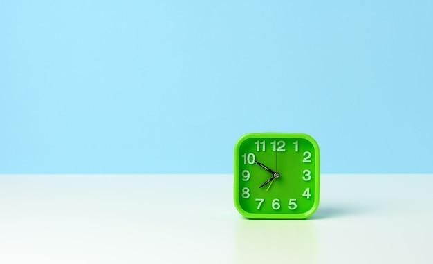 Quadratische grüne uhr mit weißen zahlen auf einem weißen tisch, zehn minuten vor acht uhr morgens, morgens