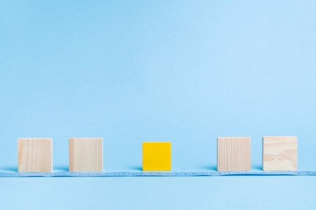 Quadratische holzblöcke stehen in einer reihe auf einer blauen oberfläche
