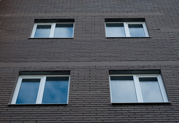 Quadratische kunststofffenster an der fassade eines neubaus