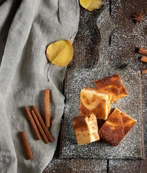 Quadratische scheiben hüttenkäse und kürbiskuchen auf einem hölzernen brett
