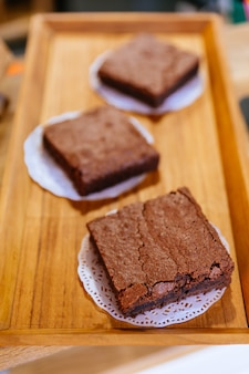 Quadratische schokoladenkuchen-schokolade backt auf hölzernem behälter dieses bereiten vor, um zu verkaufen. schmelze in deinem mund.