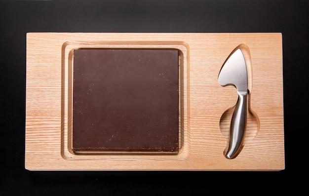 Quadratische tafel milchschokolade auf einem hölzernen brett