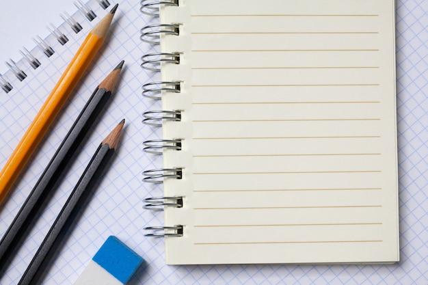 Quadratische und linierte notizbücher, bleistifte, radiergummi. das konzept ist zurück in die schule oder ins büro. speicherplatz kopieren.