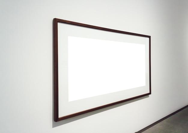 Quadratische weiße oberfläche mit dunklen rahmen, die an einer wand in einem raum befestigt sind