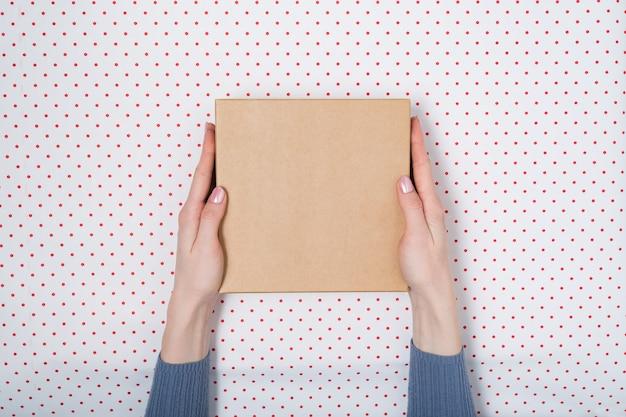 Quadratischer karton in weiblichen händen. draufsicht, weißer hintergrund
