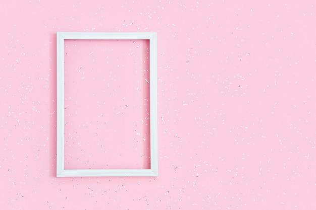 Quadratischer weißer rahmen auf rosa papierhintergrund bedeckt mit pailletten mit kopienraum. geburtstagsgrußkarte. einladung zum fest.