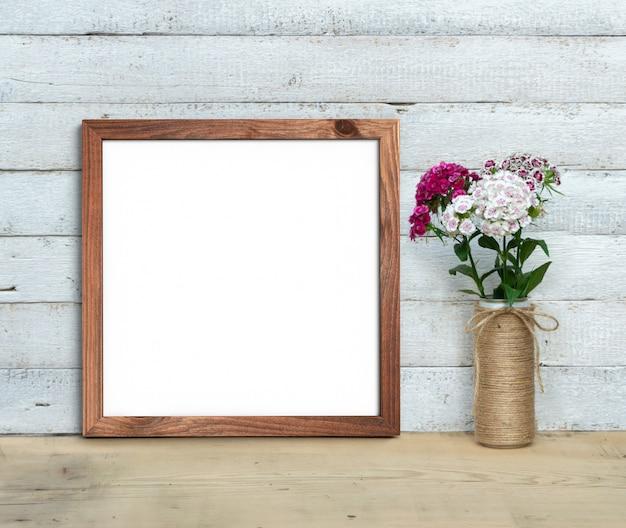 Quadratisches altes hölzernes rahmenmodell nahe einem blumenstrauß des süßen william steht auf einem holztisch auf einem gemalten weißen hölzernen hintergrund. rustikaler stil, einfache schönheit. 3d rendern.