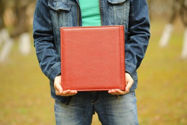 Quadratisches fotobuch in seinen händen