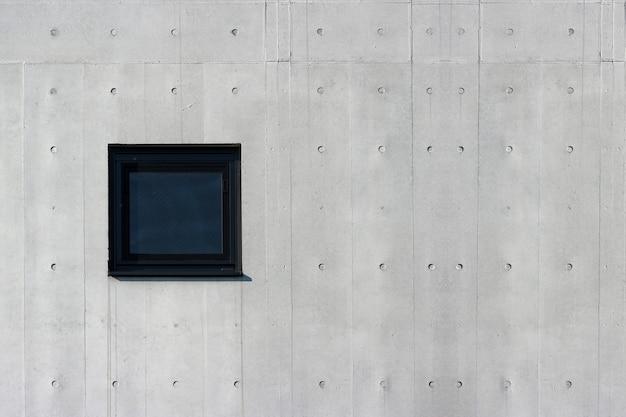 Quadratisches glasfenster auf gealtertem zementbetonmauerhintergrund. für irgendeine vintage entwurfsarbeit.