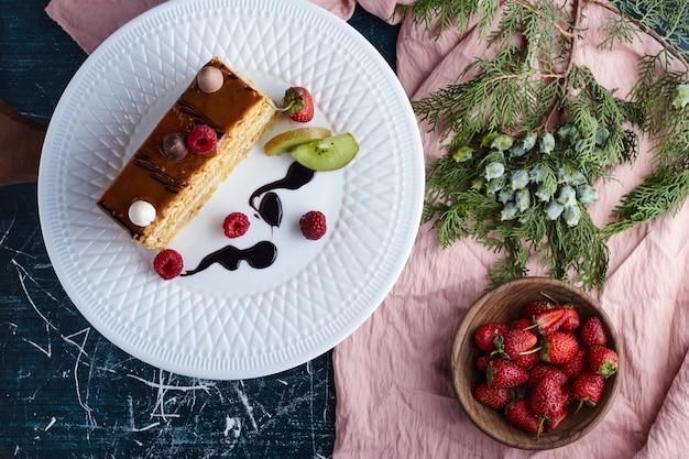 Quadratisches stück karamellkuchen mit erdbeeren, draufsicht.