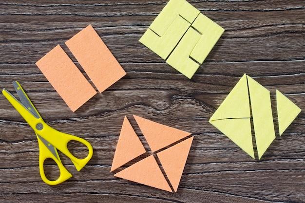 Quadratisches tangram-puzzlespiel auf einem holztisch. draufsicht.