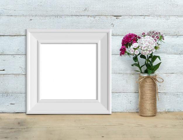 Quadratisches vintage weißes holzrahmenmodell nahe einem blumenstrauß von süßem william steht auf einem holztisch auf einem gemalten weißen hölzernen hintergrund. rustikaler stil, einfache schönheit. 3d rendern.
