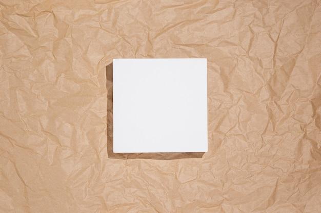 Quadratisches weißes podium für die präsentation auf zerknittertem braunem kraftpapierhintergrund. ansicht von oben, flach.